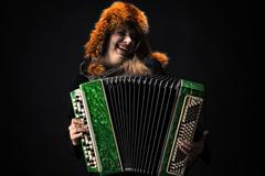 Emotional woman in fur hat playing the accordion Stock Photos