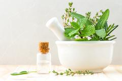 Alternative health care fresh herbal and  Bottle of aromatherapy in mortar on - stock photo