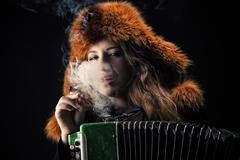 Beautiful woman in fur hat with accordion in cigarette smoke Kuvituskuvat