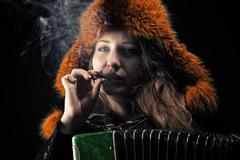 Woman in fur hat with accordion in cigarette smoke Stock Photos