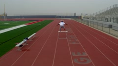 Yang Athlete Male Jumping Hurdles on a Sports  Track Stock Footage
