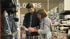 Department store seller assisting customer with buying tv set Stock Footage
