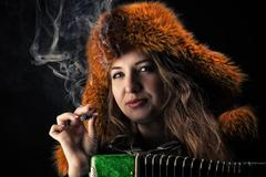portrait beautiful woman in fur hat with a cigarette in hand - stock photo