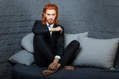 Guy with  red hair and beard, sitting on the sofa. - stock photo