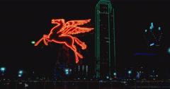 Pegasus and Dallas skyline at night Stock Footage