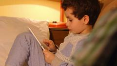 DOLLY: A little boy lays in a bed with a tablet PC - stock footage