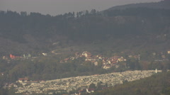 Hill with trees and a cemetery seen from distance in Sarajevo - stock footage