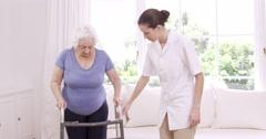 Smiling nurse helping senior woman walking Stock Footage