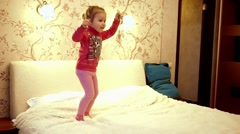 Little girl child having fun jumping on the big parent bed Stock Footage