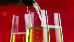 Filling flutes of champagne with golden bubbles against red bokeh background Stock Footage