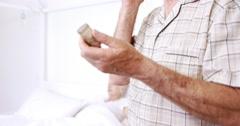 Senior man on phone call holding pills Stock Footage