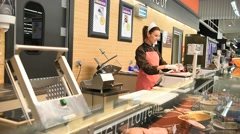 Woman pork butcher serving sausages to customer - stock footage