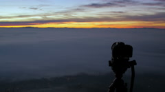 Photo camera shooting sunrise on the top of a mountain - stock footage