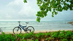 Bicycle Parked on a Tropical Beach on a Cloudy Day. Video 1080p Stock Footage