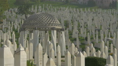 Tombstones surrounding a steel pavilion with cupola in a cemetery in Sarajevo - stock footage