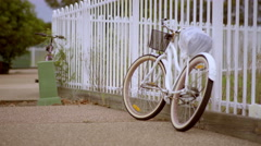 Old White Bicycle Standing Beside Fence - Color Graded 4K Resolution Stock Footage