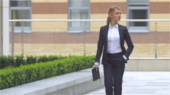 Business woman with tablet computer goes around office building. slow motion Stock Footage