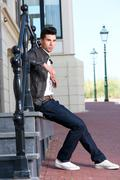 Male fashion model in leather jacket sitting outdoors - stock photo