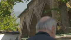 Walking by a stone buildings with arches in Sarajevo Stock Footage