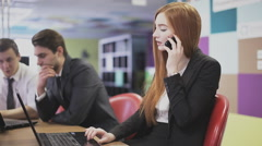 red-haired girl talking on the phone at the office - stock footage