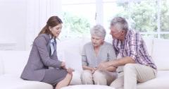 Businesswoman talking to senior couple Stock Footage