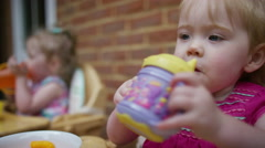 4K Cute toddler twins in high chairs eating & drinking in the backyard at home.  - stock footage