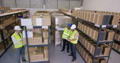 4k Workers in industrial warehouse checking stock & preparing goods for dispatch Stock Footage