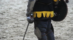 Man wearing medieval armor suit standing on battle field ready for rival attack - stock footage