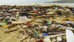 Assorted Litter and Debris Strewn along a Tropical Beach. FullHD video - stock footage