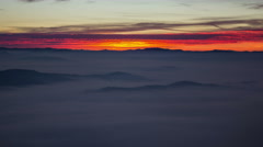 Sunrise of a mountain panorama over the city with a dense foggy layer Stock Footage