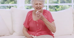 Senior woman sneezing on the sofa Stock Footage