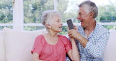 Surprised senior couple using smartphone Stock Footage
