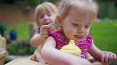 4K Little girl in high chair being tickled by her older sister Stock Footage