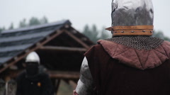 Brave warrior in steel armor waiting for enemy's attack on rainy battle field Stock Footage