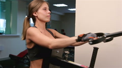 A young woman is engaged in physical activity on a sports training apparatus  - stock footage