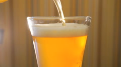 Jet of light beer fills a transparent glass on the table - stock footage