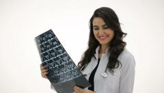 Portrait of happy female doctor looking at x ray. Backgroud white. Stock Footage