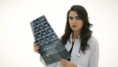Sad female doctor looking at xray. X-ray results poor. White background. - stock footage