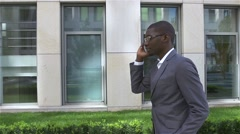 American Businessman talking on cell phone, standing in front of his office Stock Footage