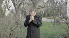Young man smokes at a park Stock Footage