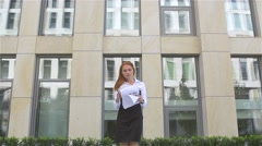 Young business woman with papers flying up, slow motion Stock Footage