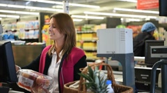 Woman cashier scanning products at grocery store cash desk - stock footage