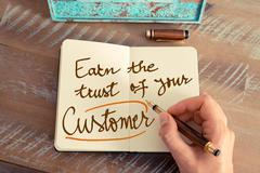 Handwritten text EARN THE TRUST OF YOUR CUSTOMER - stock photo
