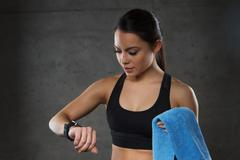young woman with heart-rate watch and towel in gym - stock photo
