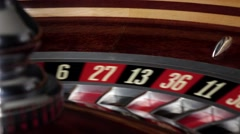 Roulette wheel running and stops with white ball on red Stock Footage