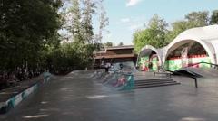 Skater make extreme jumps in skate park, slide on fence. Summer. Audience - stock footage