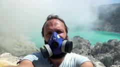 Man in gas mask taking selfie photo, video by Ijen volcano in Java, Indonesia, Stock Footage