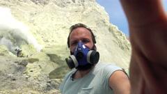 Man in gas mask taking selfie photo, video by Ijen volcano in Java, Indonesia, - stock footage