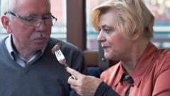Middle aged couple sharing food and feeding each other in cafe in the city Stock Footage