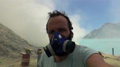 Man in gas mask taking selfie photo, video by Ijen volcano in Java, Indonesia, Stock Footage